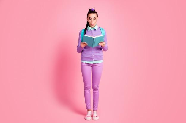 かわいい女性の完全な長さの写真は、ルックブックを驚かせた着用メガネリュックサックバイオレットプルオーバーパンツスニーカー孤立したピンク色の背景を保持します