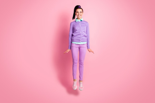 かわいい女性の完全な長さの写真ジャンプ歯を見せる笑顔の着用仕様紫ジャンパーパンツスニーカー分離ピンク色の背景