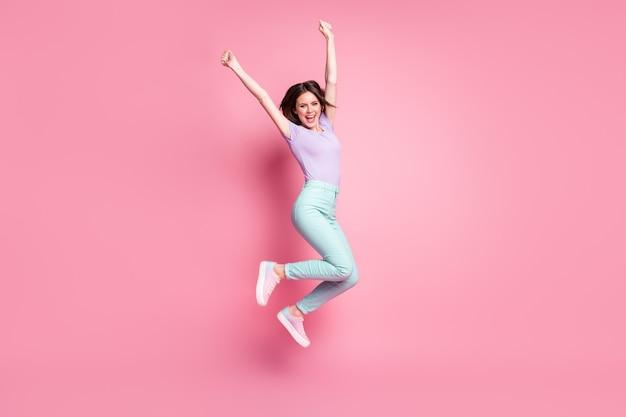 Полная фотография экстатической девушки прыгает, празднует выигрыш в лотерею, поднимает кулаки, кричит, носит фиолетовые кроссовки из бирюзовых штанов, изолированные на пастельном цветном фоне