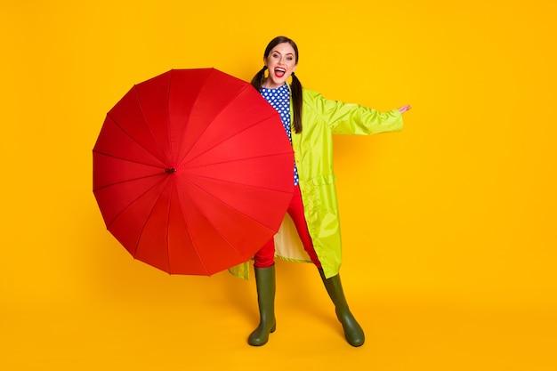 Полная длина фото восторженной девушки закрывают крышку красного зонтика, наслаждаясь дождливой весенней прогулкой, носить красные брюки, брюки, кеды, изолированные на ярком блестящем цветном фоне