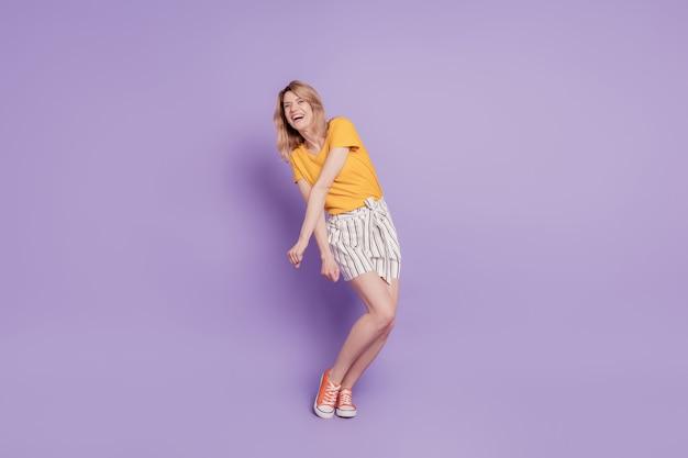 紫の背景の上に孤立して踊る熱狂的な女性の完全な長さの写真