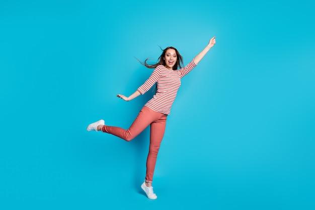 Полная длина фото возбужденной энергичной девушки, взявшись за руку, попробуй поймать мечту, зонтик, ее прическа, ветер, воздушный удар, носить хороший вид, повседневная одежда, кроссовки, изолированные на синем цветном фоне