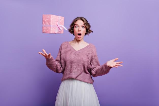 紫色の壁で踊るスカーフと長い白いスカートの魅力的な女性を楽しんでいる黒いパンストの興奮した女の子のフルレングスの写真。