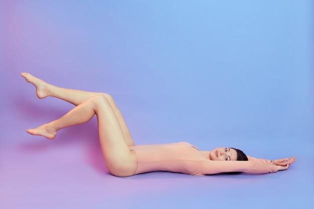 Фотография в полный рост женщины с идеальным телом, лежащей на полу и вытягивающей руки, поднимающей длинные ноги, в бежевом боди, изолированной над синей стеной с розовым неоновым светом.