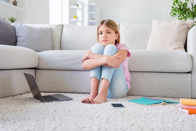 좌절한 소녀의 전체 길이 사진은 바닥 카펫에 앉아 친구를 그리워하며 집에서 원격 코로나 바이러스 검역을 연구합니다