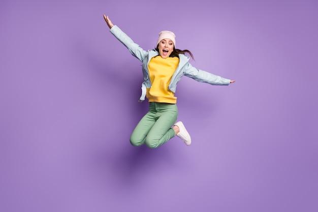 Полная длина фото фанки привлекательной леди в стильной одежде прыгать высоко радостно летающими руками, такими как крылья птица, сумасшедшая одежда, повседневная шляпа, куртка, зеленые брюки, туфли, изолированные на фиолетовом цветном фоне