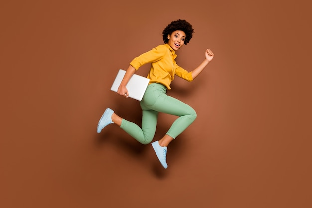 ファンキーなダークスキンの女性の全身写真ジャンプハイホールドノートブック急いでクラスレッスン女子高生着用黄色のシャツ緑のズボン靴孤立した茶色の色