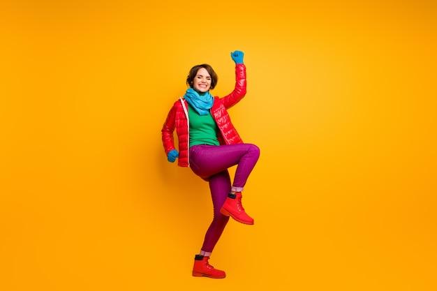 펑키 흥분된 여자의 전체 길이 사진 손을 들어 다리 황홀한 분위기 착용 캐주얼 레드 오버 코트 블루 스카프 장갑 녹색 터틀넥 바지 신발