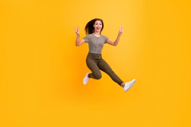 Полная фотография веселой молодой девушки, отдыхающей, расслабляющейся, весенней, свободного времени, прыжка, заставляющая v-знак носить стильную одежду, изолированную над яркой цветной стеной