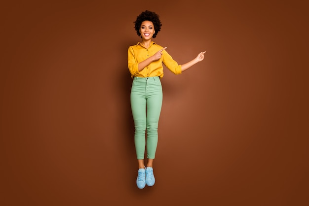 Фотография в полный рост смешной темнокожей леди, прыгающей высоко, направляя пальцы, пустое пространство, низкие цены, шоппинг, желтая рубашка, зеленые брюки, обувь, изолированный коричневый цвет