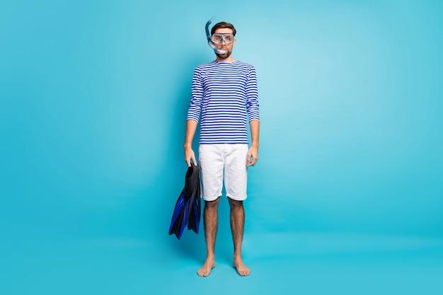 Полная длина фото забавного красивого парня, туристического дайвинга, подводная маска, дыхательная трубка, плавающие ласты глубокого использования, одетые в полосатую матросскую рубашку, шорты, изолированный синий