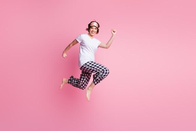 面白い女性の全身写真はピンクの壁に急いでジャンプします