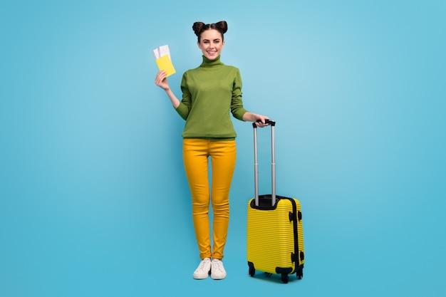 Полная длина фото забавной симпатичной женщины с билетами, документами, дешевым туром за границу, рейс, чемодан на колесиках, зеленая водолазка, желтые брюки, туфли, изолированные на стене синего цвета