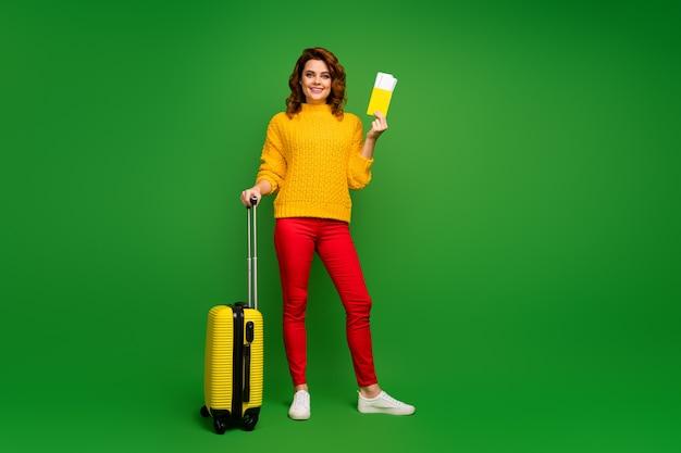 Полная фотография смешной симпатичной леди с билетами и документами. дешевый тур за границу. рейс чемодан на колесиках. желтый вязаный свитер. красные брюки. обувь. изолированная зеленая стена.