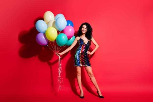 Полная длина фото девушки, держащей много воздушных шаров, выглядят пустым пространством, носят глянцевое короткое платье на высоких каблуках, изолированные на ярко-красном цветном фоне