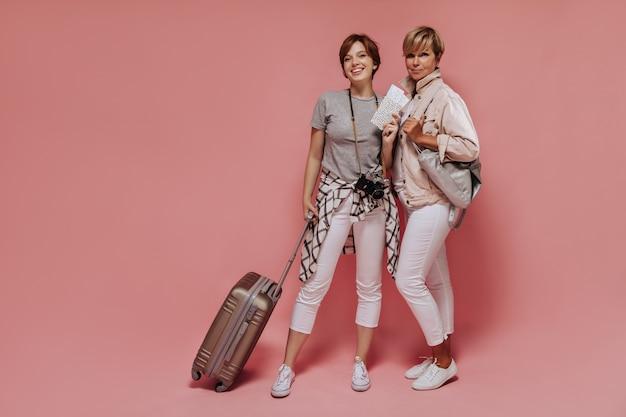 Полнометражное фото девушки в белых штанах и клетчатой рубашке, держащей билеты, камеру и чемодан и позирующей с белокурой женщиной с сумкой на розовом фоне.