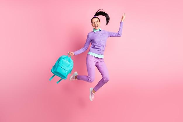 女の子のジャンプホールドバックパックの完全な長さの写真口を開けて着用仕様バイオレットジャンパーパンツスニーカー分離ピンク色の背景