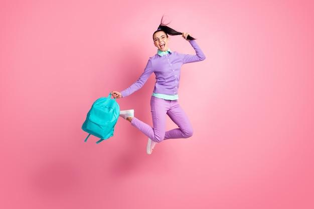 Полная длина фото девушки прыжок удерживать мешок хвост открытый рот носить очки фиолетовый пуловер брюки кроссовки изолированный розовый цвет фона