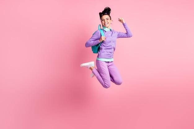 Полная длина фото девушки прыгать поднять кулаки носить сумку очки фиолетовый пуловер брюки кроссовки изолированный розовый цвет фона