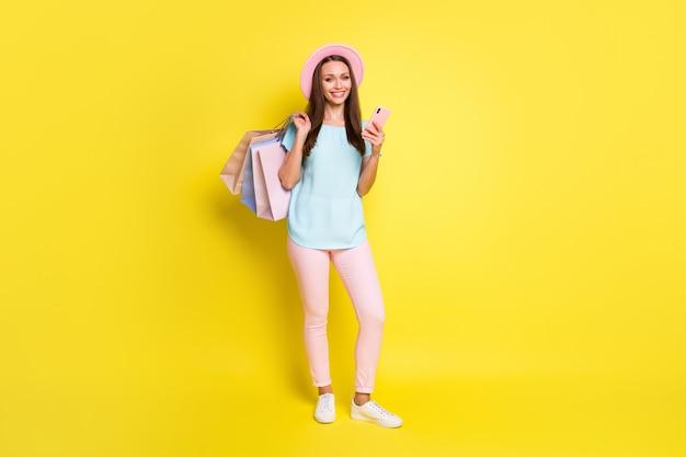 Полная фотография девушки клиента торгового центра, читающая новости о распродажах, использование смартфона, розовая синяя футболка, брюки, брюки, шляпа, кепка, изолированная на ярком блестящем цветном фоне