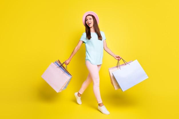 Фотография в полный рост девушки-туристки, идущей в торговый центр, впечатлен сезон, отдых, расслабление, распродажа, много сумок, синяя футболка, розовые брюки, брюки, шляпа от солнца, изолированные на ярком блестящем цветном фоне
