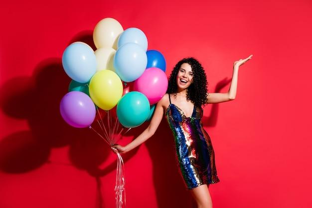 Полная длина фото великолепной девушки, держащей много воздушных шаров, поднять руку, ладонь, носить глянцевое короткое платье, изолированное ярко-красным цветом фона
