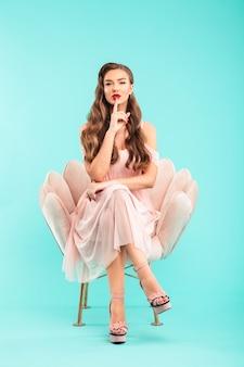 青い壁を越えて分離された足を組んで、魅惑的に唇に指を保持して柔らかいアームチェアに座っているピンクのドレスでゴージャスな女性20代の完全な長さの写真