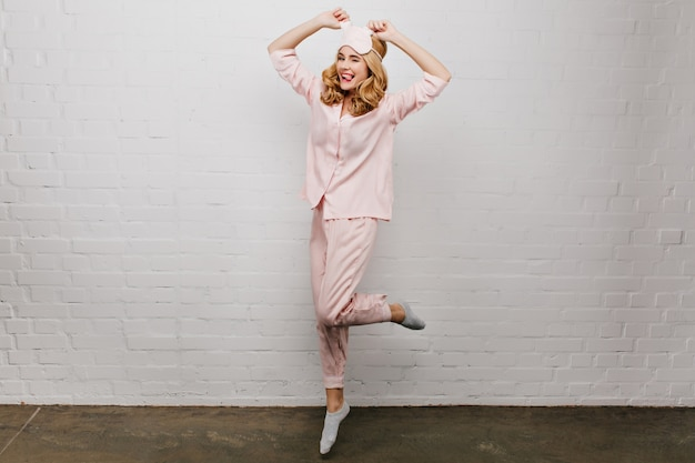 朝を楽しんでいる優雅なのんきな女の子の全身写真。見事な女性モデルは、自宅で踊る灰色の靴下とピンクのパジャマを着ています。