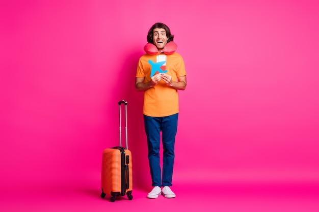 남자 가방의 전체 길이 사진 문서 종이 비행기는 목 쿠션 오렌지 티셔츠 청바지 운동화를 입고 분홍색 배경에 격리되어 있습니다.