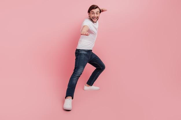 エクササイズスポーツ孤立したピンク色の背景をキックする準備ができてハンサムな魅力的な男の全身写真