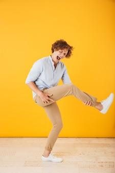 黄色の背景の上に分離された、目に見えないギターをジャンプして演奏するハンサムな巻き毛の男の全身写真