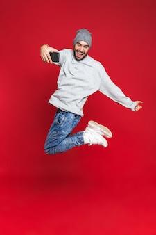 Полная длина фото красивого мужчины 30-х годов в повседневной одежде, прыгающего и делающего селфи-фото на изолированном сотовом телефоне
