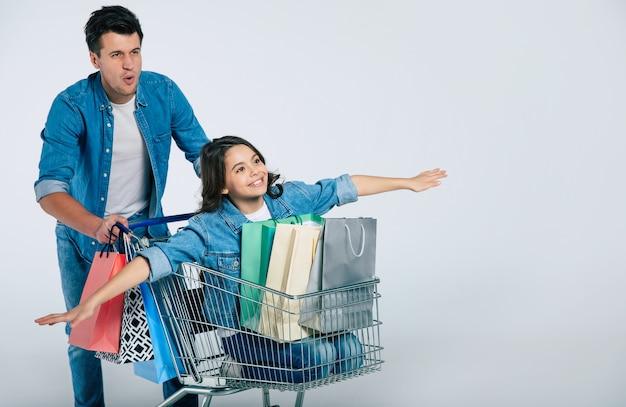비행기를 모방하는 웃는 딸과 함께 쇼핑 카트를 타는 캐주얼 복장에 행복 매력적인 남자와 그 안에 세 개의 쇼핑백의 전신 사진.