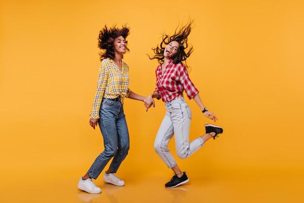 幸せな若い女性が楽しく動いているフルレングスの写真。茶色の髪のモデルは手をつないでママのジーンズで笑う