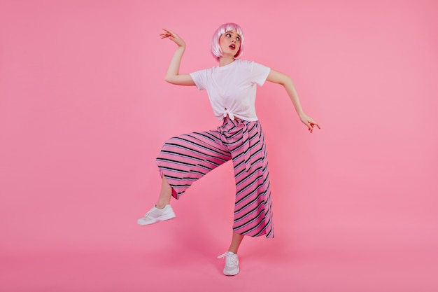 Полнометражное фото радостной девушки в перуке, которая дурачится. великолепная смешная дама в парике танцует на розовой стене