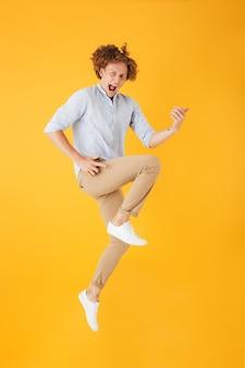 黄色の背景の上に分離された、ジャンプして目に見えないギターを弾く楽しい若い男の全身写真