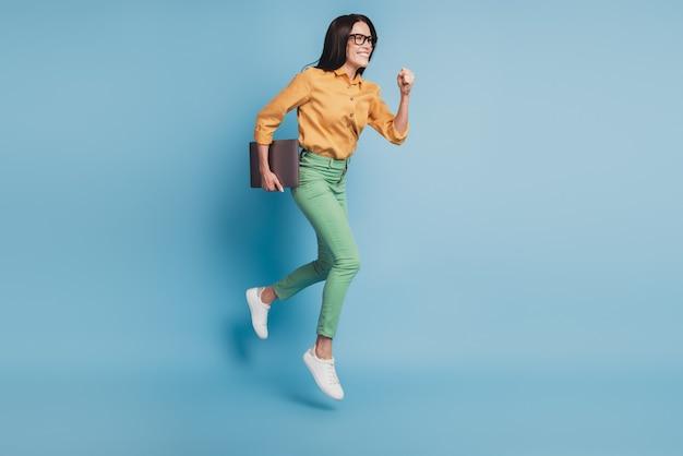 Полная длина фото прыгающей бегущей быстрой деловой женщины на синем фоне