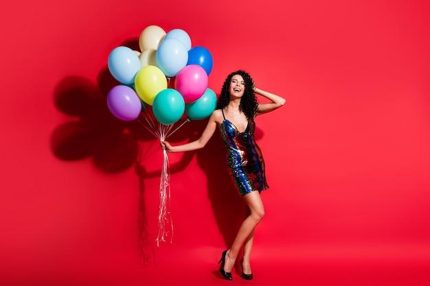 Полная длина фото дамы, держащей много воздушных шаров, рука голова носит глянцевое мини-платье на высоких каблуках, изолированных яркий красный цвет фона
