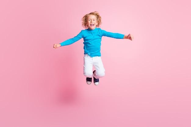 Полная длина фото маленького ребенка прыгать с открытым ртом носить синие брюки с высоким воротом, кроссовки, изолированные на пастельно-розовом цветном фоне