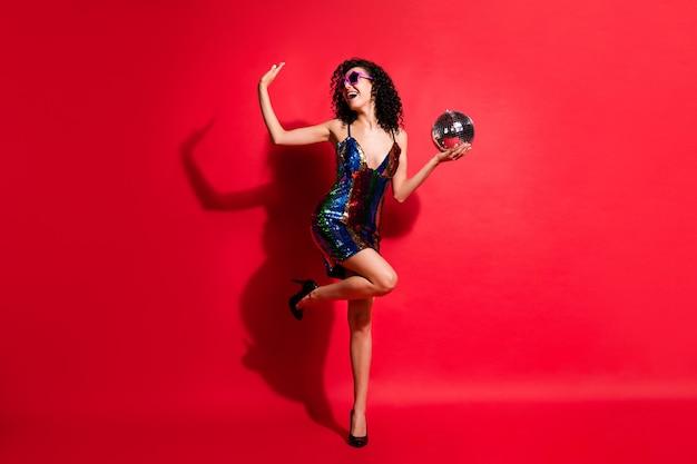 사랑스러운 소녀의 전체 길이 사진은 빛나는 공 댄스 착용 스타 선글라스 광택 짧은 드레스 신발 격리 된 붉은 색 배경