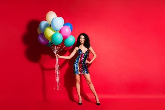 Полная длина фото прекрасной девушки, держащей много воздушных шаров, в глянцевом мини-платье на высоких каблуках, изолированном ярко-красном цветном фоне