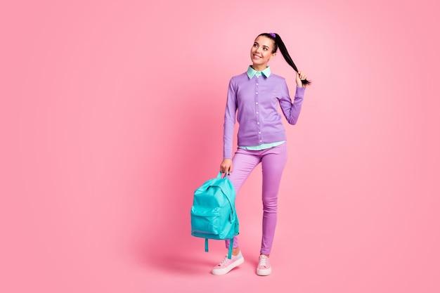 素敵な女の子の完全な長さの写真は空のスペースを保持しますバックパックを着用しますバイオレットプルオーバーパンツスニーカー孤立したピンク色の背景