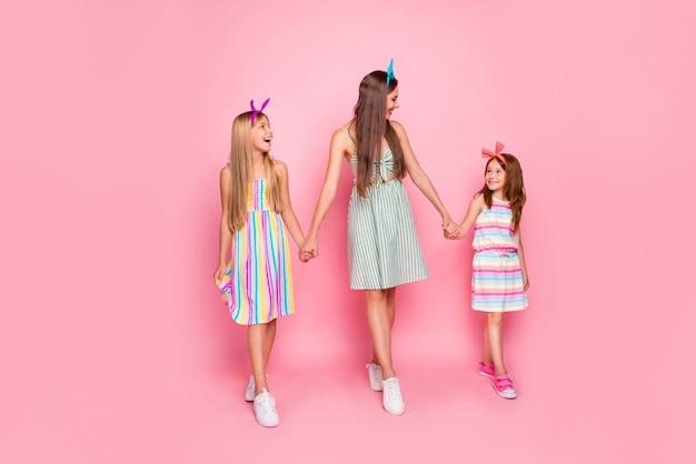 ピンクの背景で隔離のスカートのドレスを着て手をつないでいるヘッドバンドを持つ素敵な女の子の完全な長さの写真