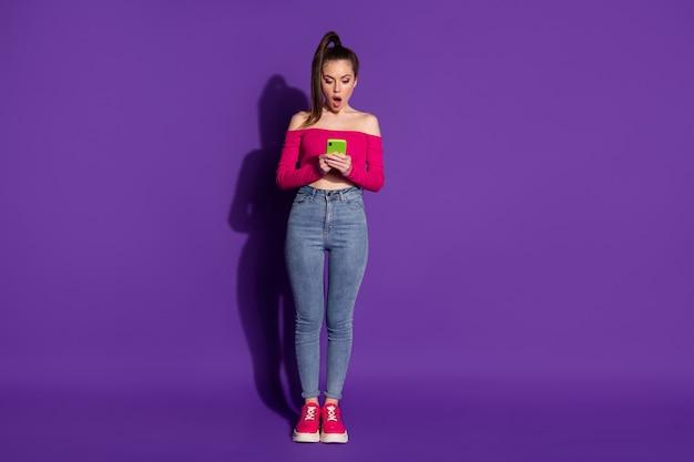 素敵な驚いた女性の手の完全な長さの写真は、携帯電話のショックを受けた摩耗ピンクの覆われていない肩トップ孤立した紫色の背景を保持します