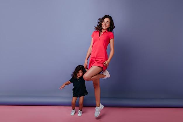 娘と踊り、笑顔で踊る壮大な若い女性の全身写真。紫色の壁に小さな女の子と手をつないで身なりのよい女性。
