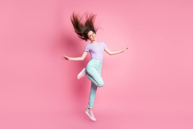 Полная длина фото милой милой милой девушки прыгает, наслаждаясь отдыхом, расслабляйтесь, носите красивую одежду, кеды, изолированные на розовом цветном фоне