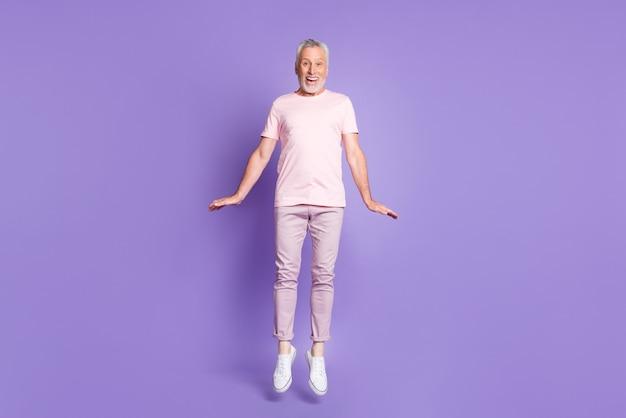 Полная длина фото старика прыгать по-детски ладони носить розовые футболки брюки кроссовки изолированный фиолетовый цвет фона