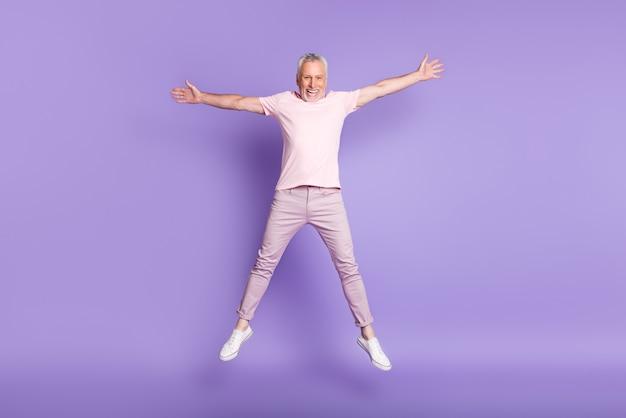 Полная длина фото пенсионера прыжок звезда поза сумасшедшая одежда розовая футболка брюки кроссовки изолированы фиолетовый цвет фона