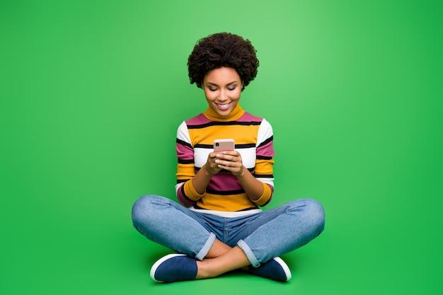 Полная длина фото позитивной афроамериканской девушки-блогера сидит, скрестив ноги, использует мобильный телефон, комментарий к публикации, репост