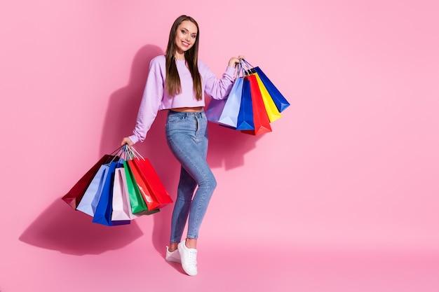 ポジティブで陽気な女の子の全身写真は、多くのバッグを持って買い物を楽しんでいます春のシーズン50%の売上高はパステルカラーの背景の上に分離されたライラックスタイルのスタイリッシュなトレンディなジャンパーを着用します